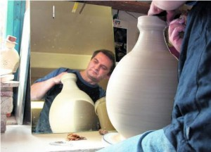 Der Töpfer Ingo Müller dreht in seiner Werkstatt in Haina eine große bauchige Vase. Im Spiegel kann er das Werkstück einfacher überprüfen. Foto: C. Hoppe