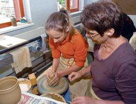 Die Drehscheibe probierte auch die zwölfjährige Anna aus Schwarzbach aus. Keramikerin Ramona Grimm gibt dabei Hilfestellung. Foto: Swietek